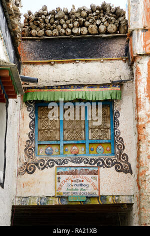 Ornate window on the wall of a Tibetan house in Lo Manthang, Upper Mustang region, Nepal. Sign for a souvenir shop on the lower part of the image. - Stock Image