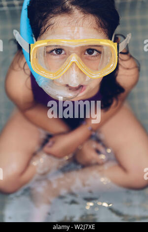 vertical portrait of a serious beautiful little girl sitting with snorkel goggles in the tub while taking a bath in the bathtub, kids hygiene concept, - Stock Image