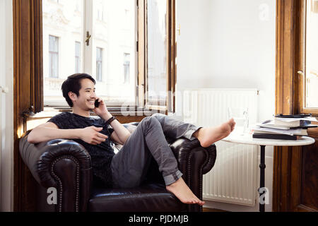 Mid adult man sitting on armchair chatting on smartphone - Stock Image