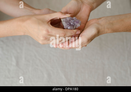 Womans hands holding and placing an amethyst crystal in another womans hands in healing gesture. - Stock Image