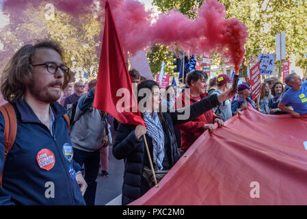 London, UK. 20th October 2018. A woman holds a red smoke flare as the giant flag reaches Dwoning St at the end of the People's Vote March calling for a vote to give the final say on the Brexit deal or failure to get a deal. They say the new evidence which has come out since the referendum makes it essential to get a new mandate from the people to leave the EU. With so many on the march the crowding meant many failed to reach Parliament Square and came to a halt in Whitehall. Peter Marshall/Alamy Live News - Stock Image