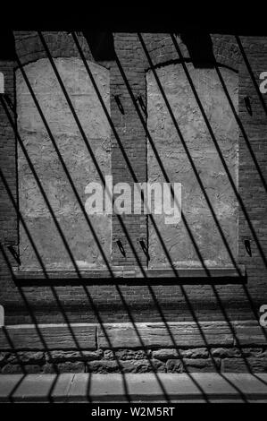 Diagonal shadows make an interesting pattern over two boarded up windows - black and white - Stock Image