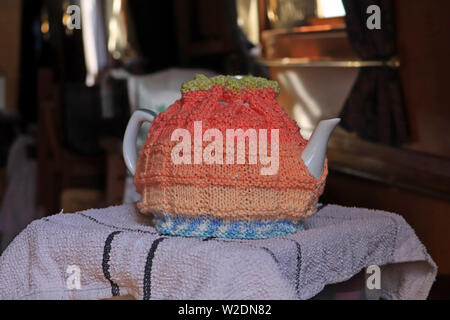 A hand knitted tea cosy in orange, green and blue shades of yarn that is in use on a large tea pot.  The tea cosy has a draw string around the top - Stock Image
