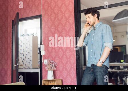 Mid adult man talking on phone - Stock Image