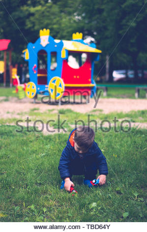 Small boy picking up two plastic toy locomotives - Stock Image