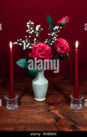 Beautiful pink roses in a vase acsented with Baby's Breath flowers, Two red candles in crystal holder. - Stock Image