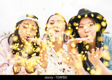 Happy Asian friends doing party throwing confetti outdoor - Young people having fun celebrating at festival event outside - Stock Image