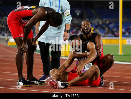 YOKOHAMA, JAPAN - MAY 12: Jereem Richards hugs fellow teammate Machel Cedenio (sitting) after he helped win the mens 4x400m relay final Day 2 of the 2019 IAAF World Relay Championships at the Nissan Stadium on Sunday May 12, 2019 in Yokohama, Japan. (Photo by Roger Sedres for the IAAF) - Stock Image