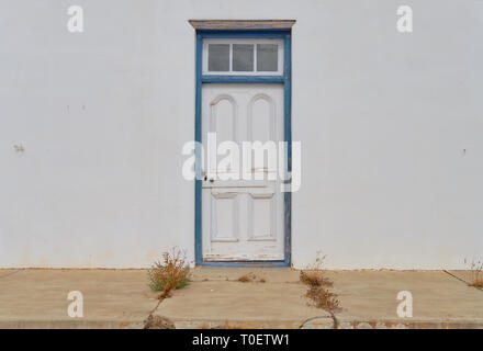 Minimalist capture of a single rural door on a white textured wall.  Door has blue frame in a state of needing repairs. Front concrete porch with weed - Stock Image