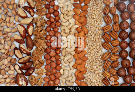 background from a mixture of nuts on a light background. view from above - Stock Image