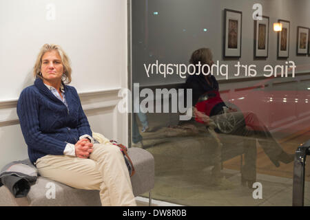 Huntington, New York, U.S. - March 1, 2014 - A visitor sits on a bench near the front window at the Opening  Reception '3 Wild & Crazy Artists' at FotoFoto Gallery. © Ann E Parry/Alamy Live News - Stock Image
