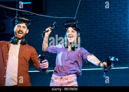 Man and woman simulating weightlessness with virtual reality headset and gamepads in the dark room of the playing club - Stock Image