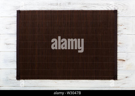 Empty Asian Food Background. Dank Bamboo mat on wooden background top view with copy space flat lay. - Stock Image