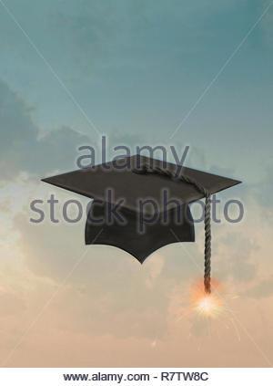 Burning fuse on mortarboard tassel - Stock Image
