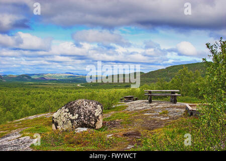 Wooden benches and a table invite to a picnic overlooking the tundra between Neiden and Bugoyfjord in the Varanger - Stock Image