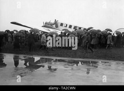 The military airport in Cologne that has been established in 1912 opened for civilian operation in 1926. Onlookers stand around a Junkers G 24. - Stock Image
