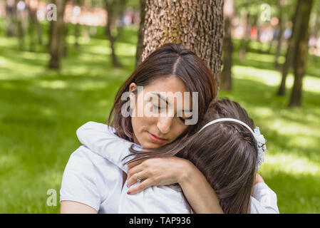 Young mom hugs daughter showing love and support, caring young mother embrace girl.Happy mother hugging her daughter with love and natural emotion smi - Stock Image