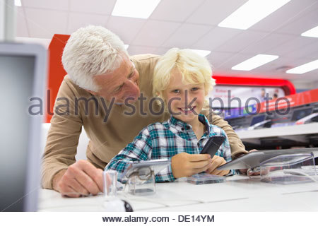 Portrait of smiling grandson looking at cell phones with grandfather in electronics store - Stock Image