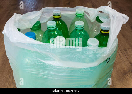 Detail of empty plastic bottles in a carrier bag on wooden floor. Ecological sorting and disposal of household waste. Contamination of e environment. - Stock Image