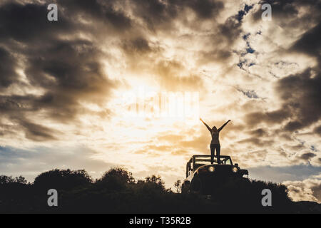 Success and lonely traveler concept with girl in silhouette standing on his car and opening arms up to the dramatic sky of a golden sunset - outdoor t - Stock Image