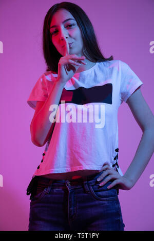 Teen girl putting finger up to lips and saying shh, isolated on colorful pink background in studio. Women's secrets concept. Low key, close up - Stock Image
