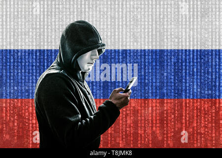 Russian hooded hacker with mask holding smartphone - Stock Image