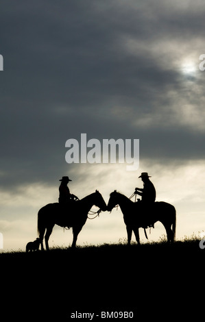 Cowboy and cowgirl on their horses at sunset - Stock Image