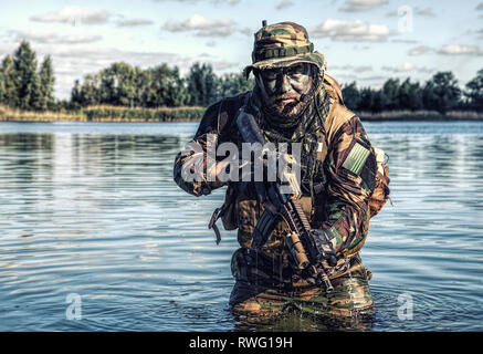 Bearded soldier of special forces in action during a river raid in the jungle terrain. - Stock Image