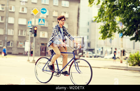 young hipster man with bag riding fixed gear bike - Stock Image