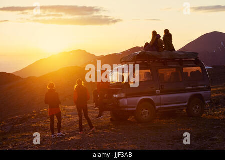 Friendship and travel concept with group of five friends sitting and standing near car on mountain top at sunset - Stock Image