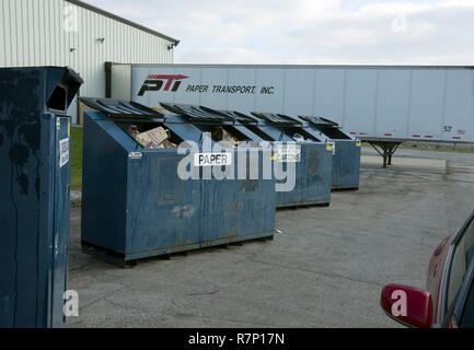 Collection bins for paper, plastic bottles, and cardboard at community recycling center. - Stock Image