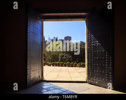 13th century Alhambra from the open studded doors of the Palacio de los Cordova in the Albaicín district of the City of Granada, Andalucia, Spain. - Stock Image