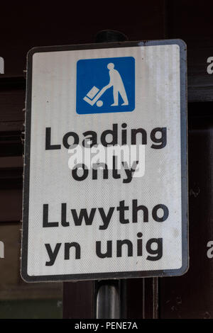 Bilingual street sign in English and Welsh indicating parking for loading only or llwhytho yn unig Wrexham Wales June 2018 - Stock Image