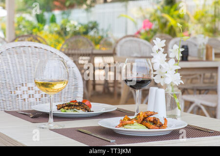 A luxurious lunch table with grilled prawns, chicken and wine. - Stock Image