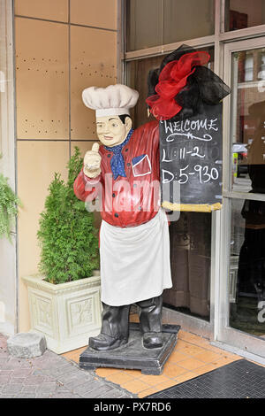 Large chef statue or figure on the sidewalk holding a restaurant sign board showing the hours of operation at a cafe in LaGrange Georgia, USA. - Stock Image
