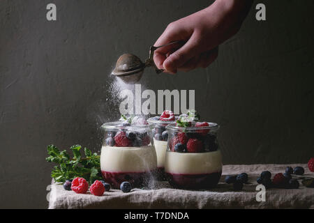 Homemade classic dessert Panna cotta with raspberry and blueberry berries and jelly in jars, decorated by mint with sprinkling sugar powder over linen - Stock Image