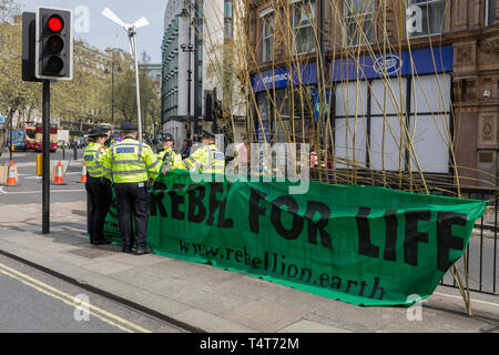 Met police officers talk at a banner on the north end of Waterloo Bridge on day 4 of protests by climate change environmental activists with pressure group Extinction Rebellion, on18th April 2019, in London, England. The Met have been criticised for allowing the protests to continue their occupations of major roads and junctions such as Waterloo Bridge and Oxford Circus. - Stock Image