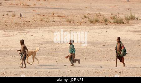 Africa, Namibia, Opuwo. Three Himba boys and dog. Credit as: Wendy Kaveney / Jaynes Gallery / DanitaDelimont.com - Stock Image