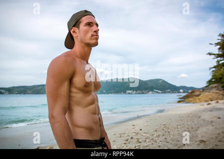 Handsome young man on beach with baseball cap - Stock Image