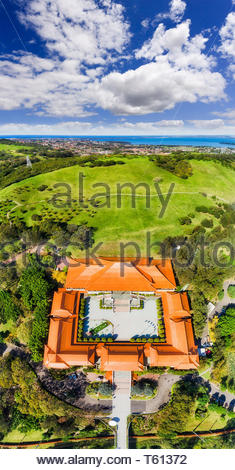 Vertical panorama over tiles of red roofs surrounding inner yard of Nan Tien Buddhist temple and monastery on green hill side around Wollongong in aer - Stock Image