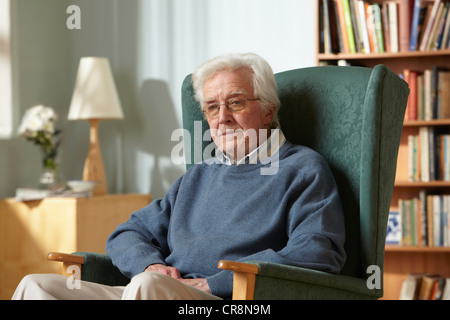 Senior man in armchair, portrait - Stock Image