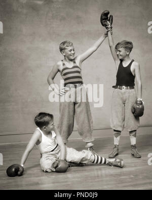 1930s TWO BOYS BOXING A THIRD DECLARING ONE THE WINNER THE DEFEATED LOOSER IS SITTING ON THE FLOOR - b8248 HAR001 HARS FITNESS JUVENILE STYLE FEAR HEALTHY REFEREE BALANCE COMPETITION ATHLETE KNICKERS LIFESTYLE SATISFACTION CELEBRATION BROTHERS ATHLETICS FRIENDSHIP FULL-LENGTH PHYSICAL FITNESS WINNER INSPIRATION MALES RISK ATHLETIC SIBLINGS CONFIDENCE B&W GOALS SUCCESS ACTIVITY HAPPINESS PHYSICAL PROTECTION STRENGTH TROUSERS VICTORY COURAGE EXCITEMENT LEADERSHIP PRIDE ON THE AUTHORITY SIBLING THIRD CONCEPTUAL ATHLETES BOXING GLOVES FLEXIBILITY MUSCLES STYLISH DECLARING KNEE PANTS KNICKERBOCKERS - Stock Image