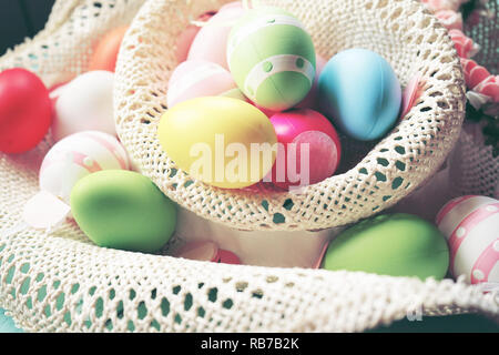A beautiful and colorful close-up of easter eggs in plain pastel colors and striped in a basket with flowers - Stock Image