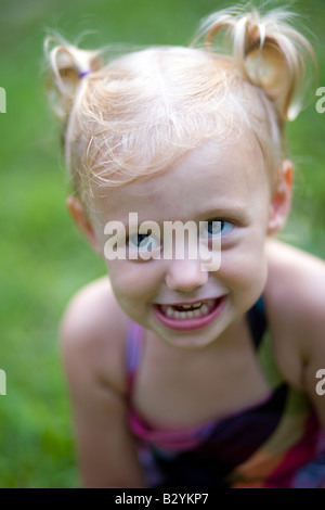 A two-year-old girl with pig tails in her hair smiles with a devilish grin. - Stock Image