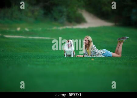 Young beautiful woman girl lady blond hair with red lips in casual style with english bulldog. Woman plays with dog, laughing, happy and inspired walk - Stock Image