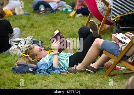 Young woman lying on the grass reading a book relaxing outside in the garden area at Hay Festival 2018 Hay-on-Wye Powys Wales UK - Stock Image