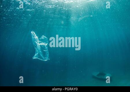 An underwater image of a plastic bag drifting in the ocean - Stock Image