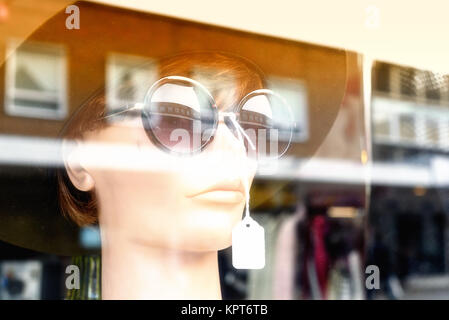 Mannequin model wearing sunglasses and a summer hat stares out from a shop window with nobody - Stock Image