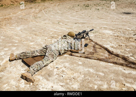 Young male sniper in camouflage with gun in the desert. - Stock Image