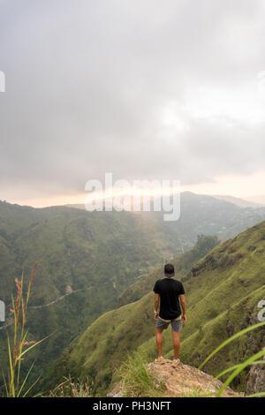 Travel concept. Man watching sunrise on Small Adams peak top in Ella, Sri Lanka - Stock Image